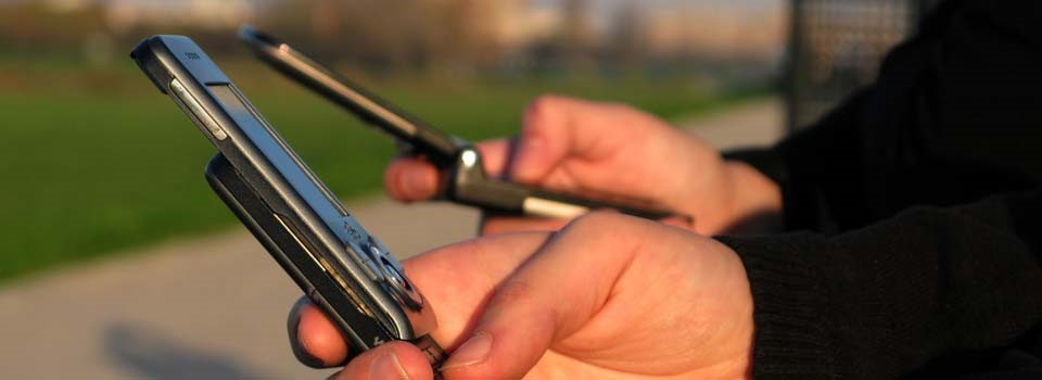 People using mobile phones to show how businesses can use SMS for marketing