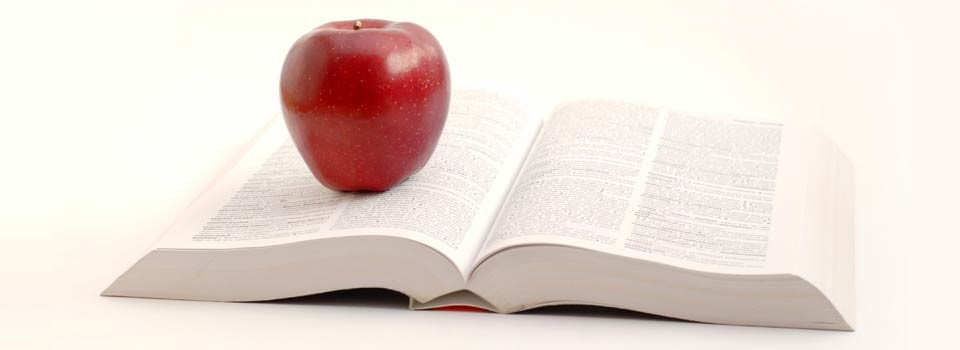 Image of an apple sitting on a book to reflect how school and parent communication can be improved with SMS
