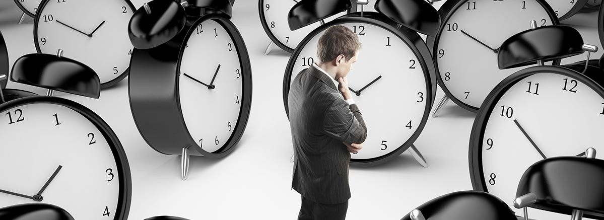 Businessman looking at oversized clocks pondering time saving through SMS