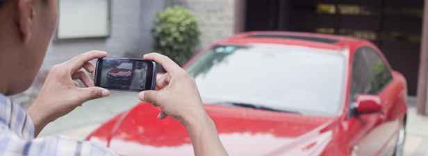 Picture texts in action - a man taking a photograph of his car and sending an MMS